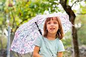 Cute little girl holding an umbrella outdoors.
