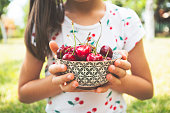 Little child holding bowl of cherries. Concept of healthy eating.