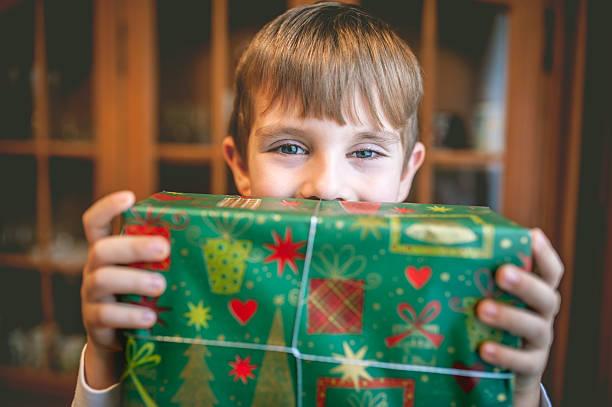 kind hält weihnachtsgeschenk - weihnachten 7 jährige stock-fotos und bilder