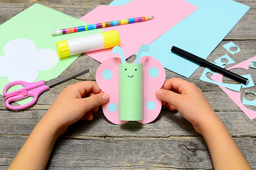 Child shows a fun paper diy. Stationery on an old wooden background. Preschool paper and glue crafts activities. Children creative abilities development