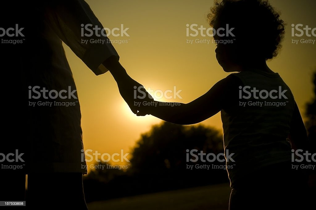 Child Holding Hands of her Mother at Sunset royalty-free stock photo