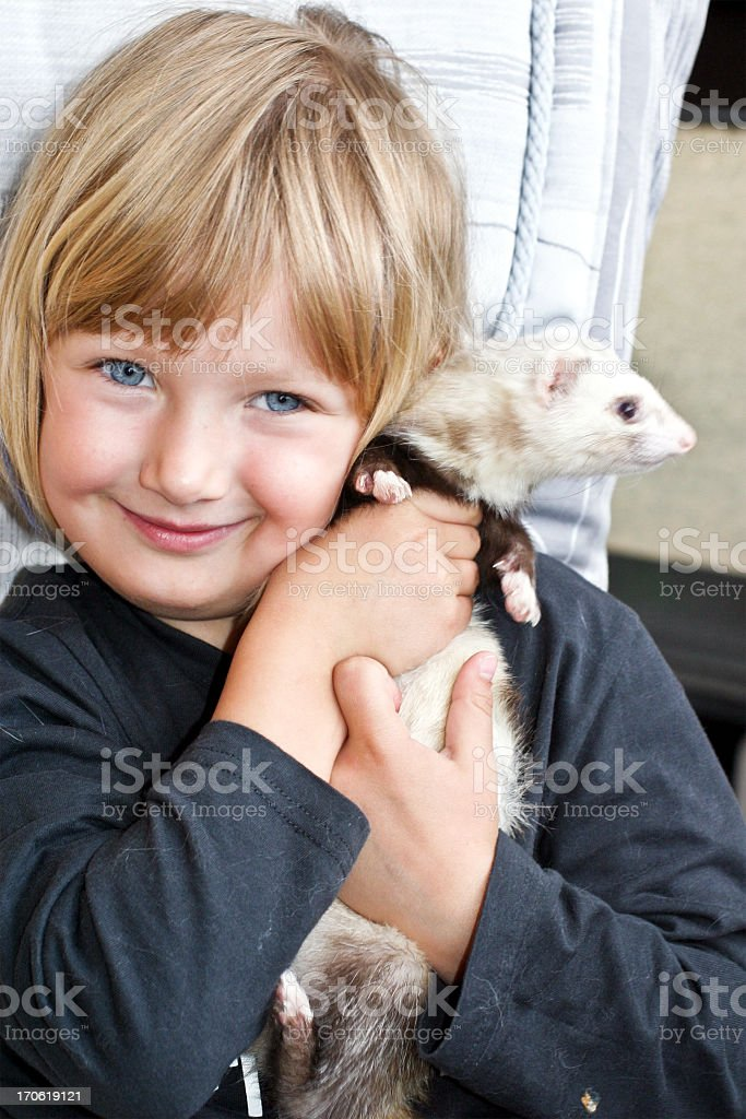 Child holding her pet ferret as her friend stock photo
