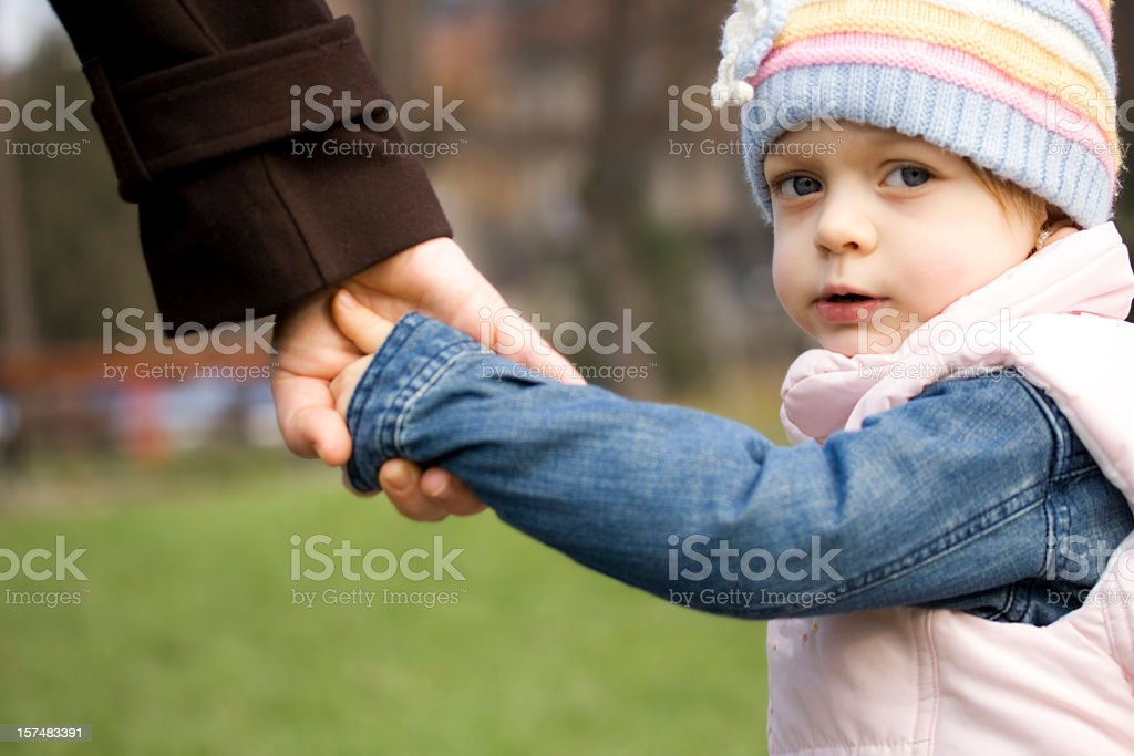 Child holding mother's hand stock photo