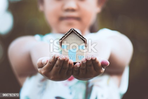 istock Child holding paper house in hands as real estate and family home concept 966782970