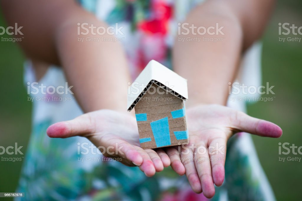 Child holding paper house in hands as real estate and family home concept Child holding paper house in hands as real estate and family home concept Adult Stock Photo