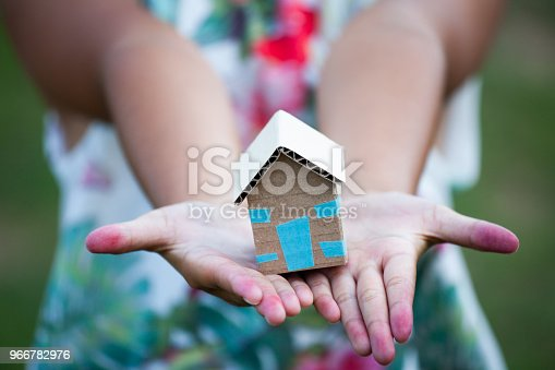 istock Child holding paper house in hands as real estate and family home concept 966782976