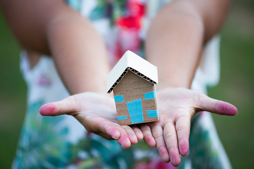 Child Holding Paper House In Hands As Real Estate And Family Home Concept Stock Photo - Download Image Now