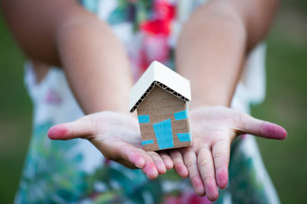 Child holding paper house in hands as real estate and family home concept Child holding paper house in hands as real estate and family home concept sheltering stock pictures, royalty-free photos & images