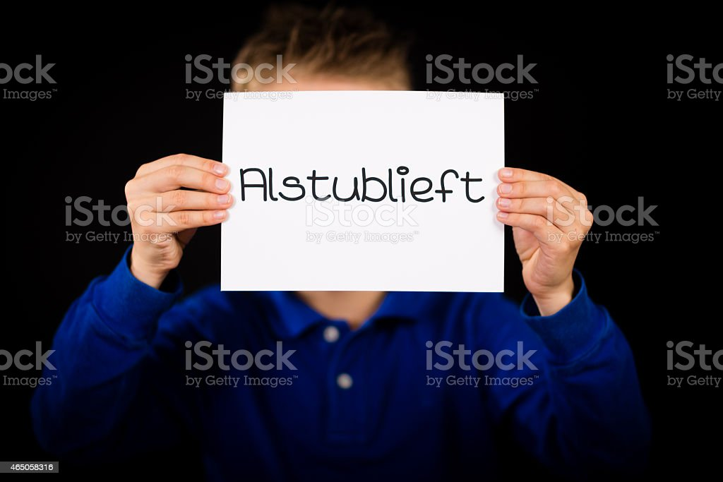 Child holding sign with Dutch word Alstublieft - Please stock photo