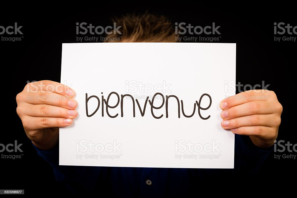 Child holding sign with French word Bienvenue - Welcome stock photo