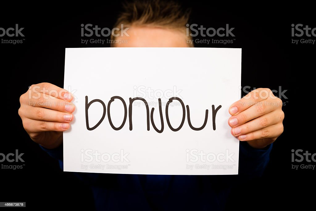 Child holding sign with French word Bonjour - Hello stock photo