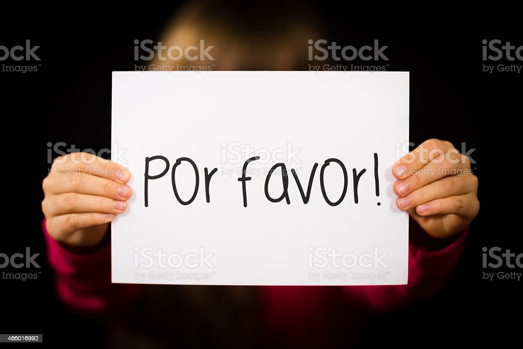 Child holding sign with Spanish words Por Favor - Please stock photo