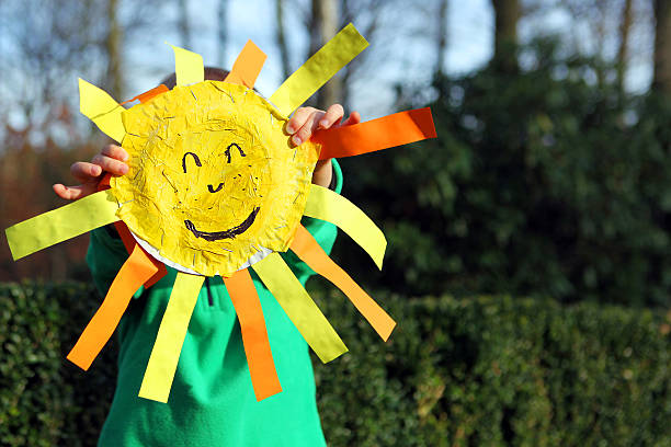 Child Holding Smiley Face Sun Outdoors stock photo