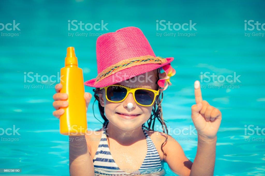Kind hält Sonnencreme – Foto