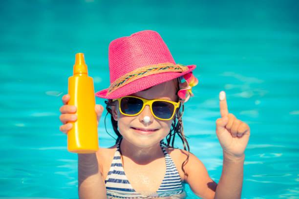 Criança segurando loção protetor solar - foto de acervo