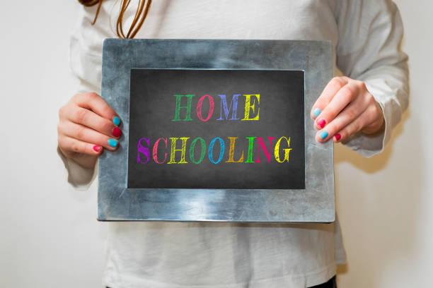 kind hält eine tafel mit dem wort homeschooling - homeschooling stock-fotos und bilder