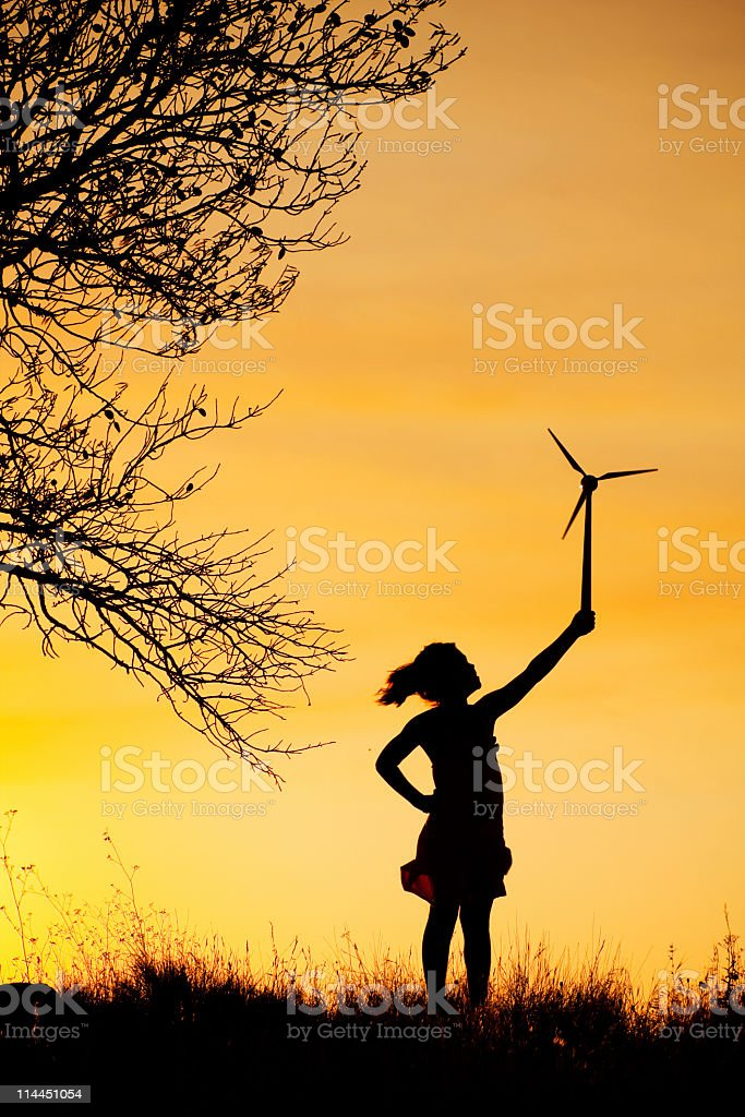 Child holding up a small wind turbine. royalty-free stock photo