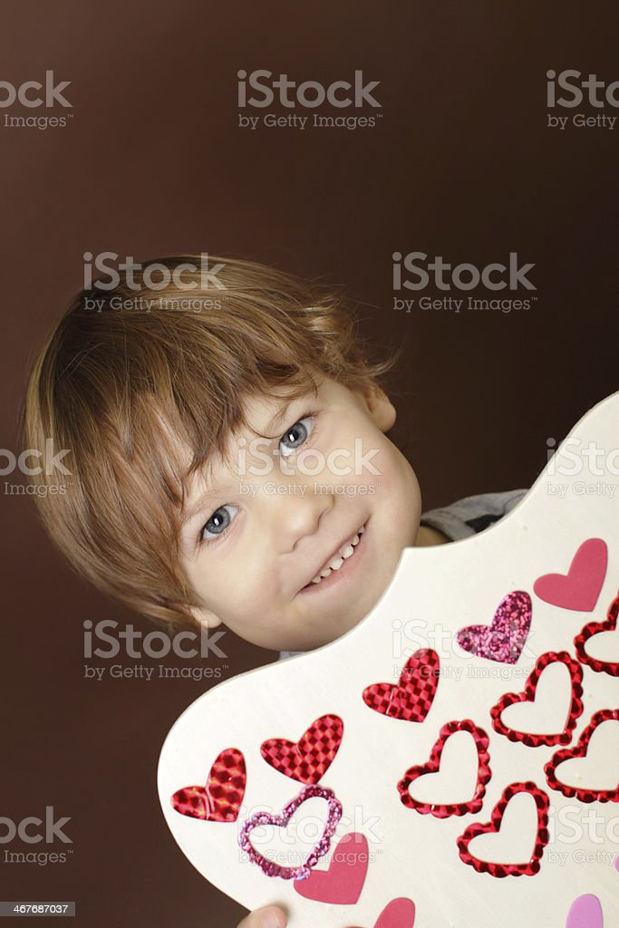 Child holding Valentine's Day Craft with Hearts stock photo