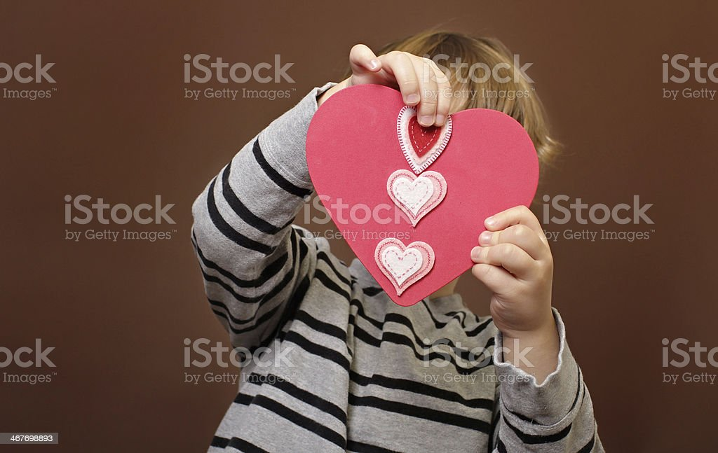 Child holding Valentine's Day Craft with Hearts royalty-free stock photo