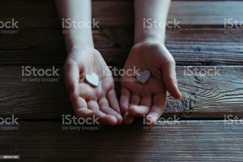 孩子手捧著白色的心在一張木桌上。 免版稅 stock photo