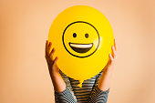 istock Child holding yellow balloon in the hands 1207314090