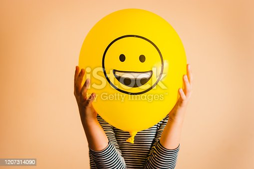 Unrecognizable person holding yellow balloon against orange background.