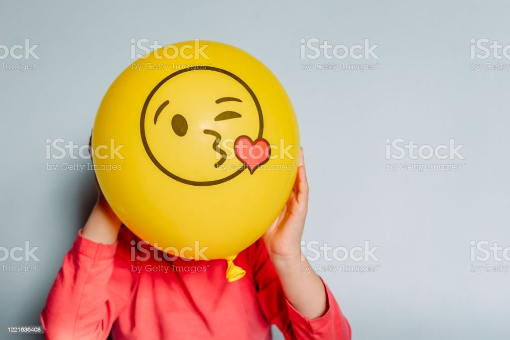Child holding yellow balloon in the hands Unrecognizable person holding yellow balloon against blue background Anthropomorphic Face Stock Photo