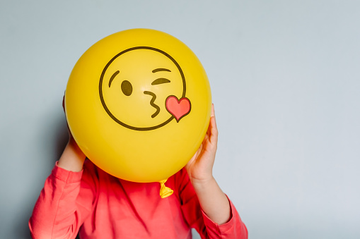 Child Holding Yellow Balloon In The Hands Stock Photo - Download Image Now