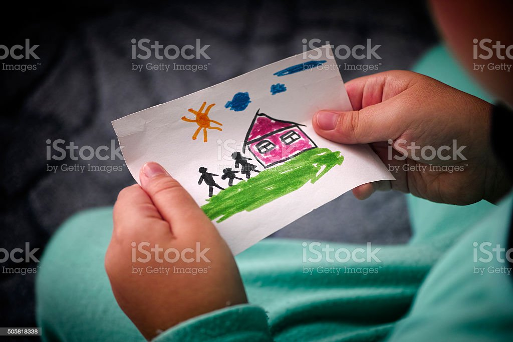 Child holds a drawn house with family stock photo