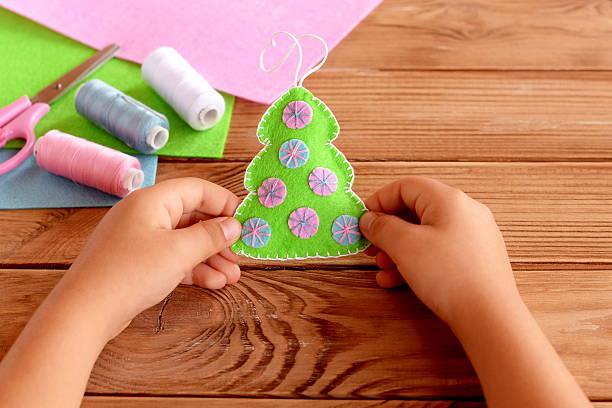 child holds a felt christmas tree in his hands - diy xmas stock-fotos und bilder