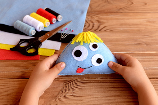 Child holds a felt monster in his hands