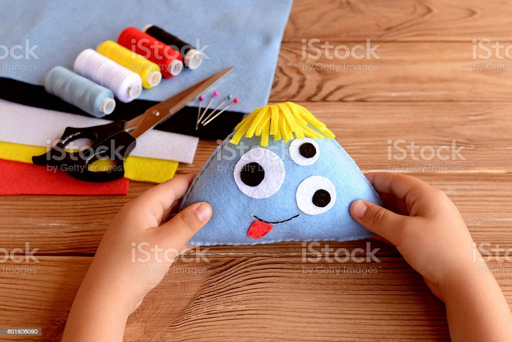 Child holds a felt monster in his hands stock photo