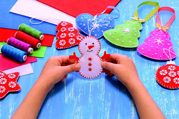 child holds a felt snowman ornament in his hands - filzen kinder stock-fotos und bilder