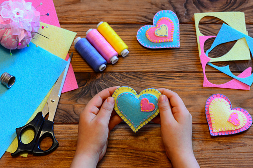 Child holds a felt valentine in his hands. Child made valentines from felt. Valentines day crafts idea. Felt heart ornaments, scissors, thread, felt sheets on a wooden table. Sewing craft projects