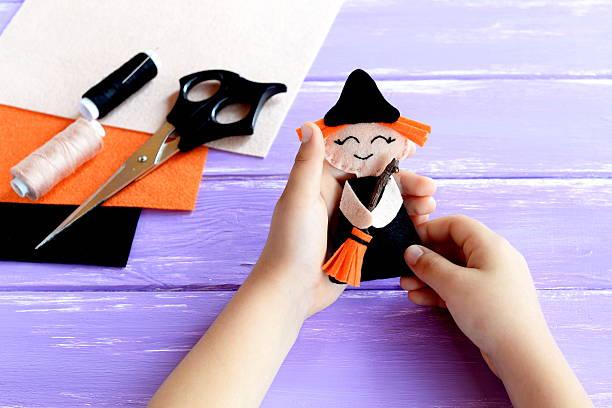 child holds a halloween witch doll in his hands - nähpuppen stock-fotos und bilder
