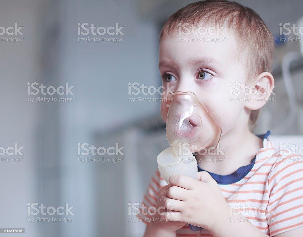 child holds a mask vapor inhaler stock photo