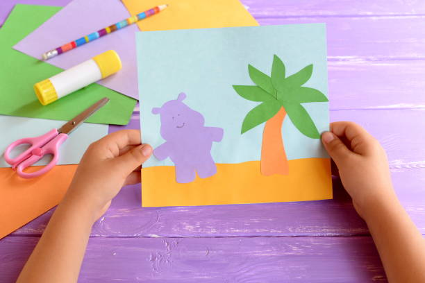 a child holds a paper card with a hippo and a palm tree. colored paper sheets, scissors, pencil, glue stick. cute and easy hand craft for preschoolers. card making step by step - kids holding hands zdjęcia i obrazy z banku zdjęć