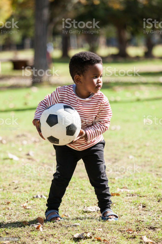Child holds a soccer ball while playing at the park. stock photo