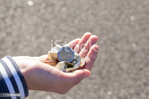 istock A child holds coins and euro notes in his hands. Pocket money image. 1124554496