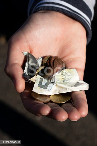 istock A child holds coins and euro notes in his hands. Pocket money image. 1124554595