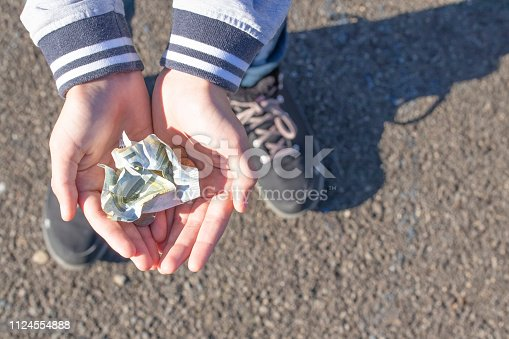 istock A child holds coins and euro notes in his hands. Pocket money image. 1124554888