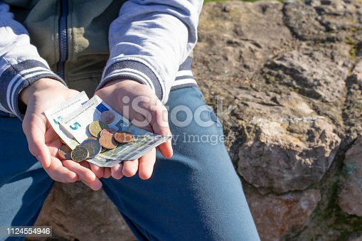 istock A child holds coins and euro notes in his hands. Pocket money image. 1124554946
