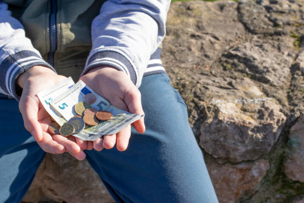 A child holds coins and euro notes in his hands. Pocket money image. A child holds coins and euro notes in his hands. Pocket money image. Poor low-income family, the concept of poverty, begging allowance stock pictures, royalty-free photos & images