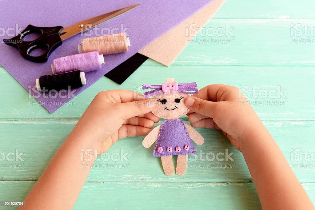 Child holds felt doll in hands and shows it stock photo