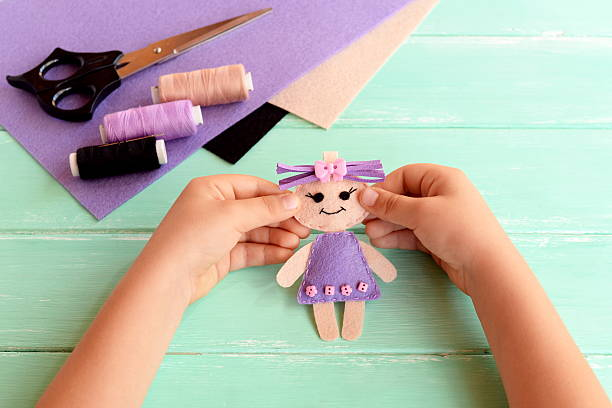 child holds felt doll in hands and shows it - filzen kinder stock-fotos und bilder