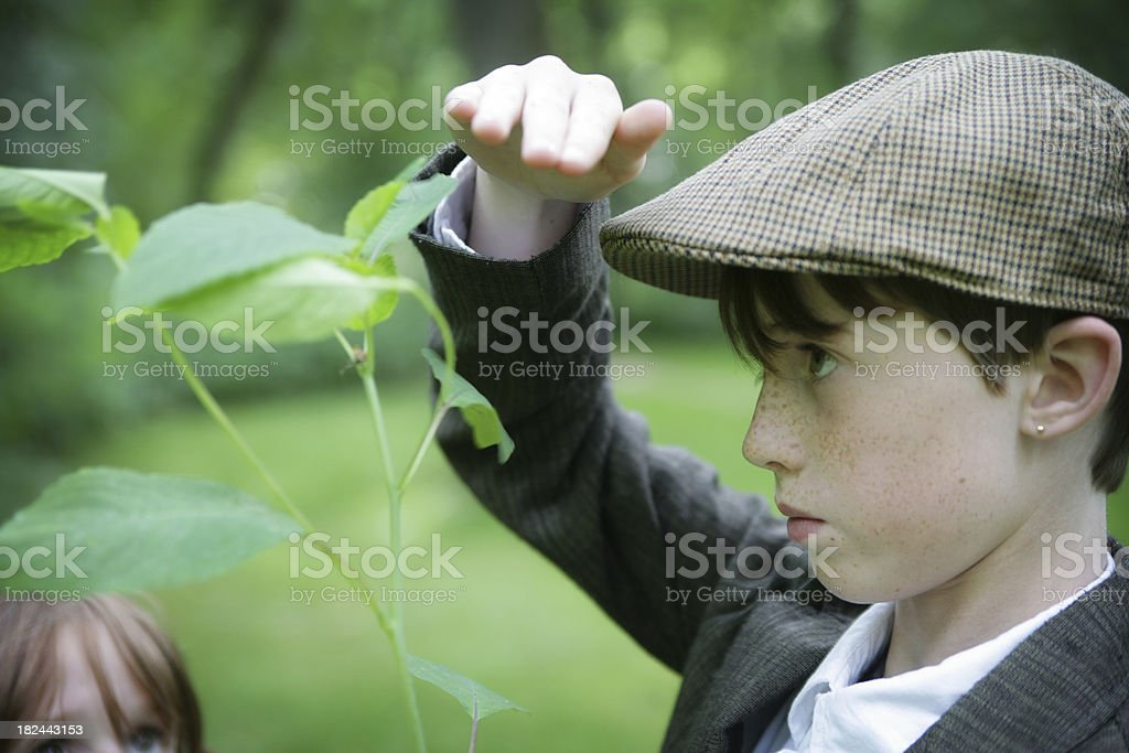 Child Holds Hand Up to Measure His Height with Plant stock photo