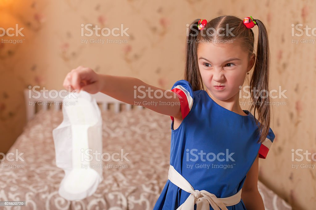 Child holds panty liners in her hand. stock photo
