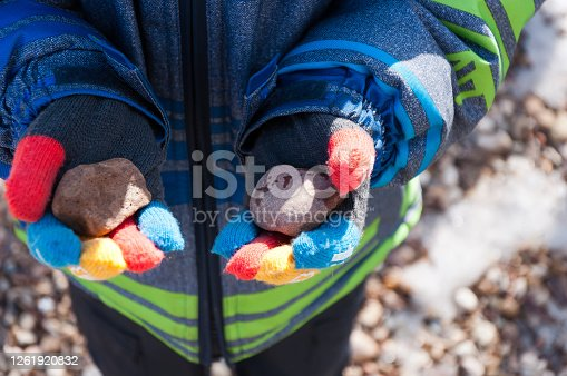 Boy holds stones in multi-colored gloves.