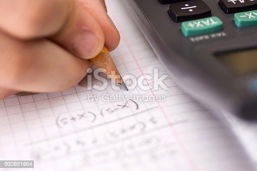 istock Child Holds the Pencil in his Hand and Solves Mathematical Problems. School, Education and Learning Concept. 932651654
