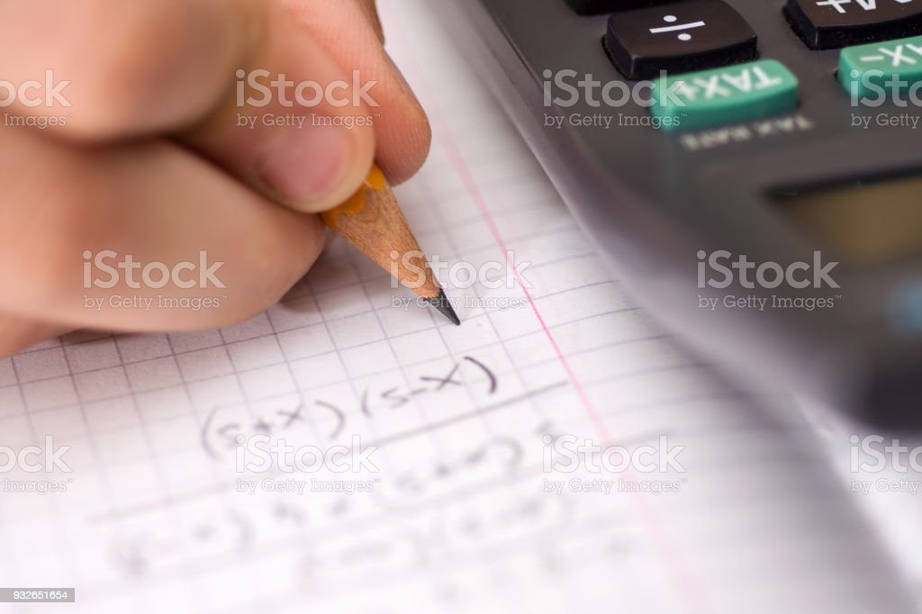 Child Holds the Pencil in his Hand and Solves Mathematical Problems. School, Education and Learning Concept. stock photo